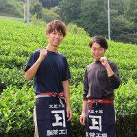 受賞者の2名が茶畑の前でポーズ